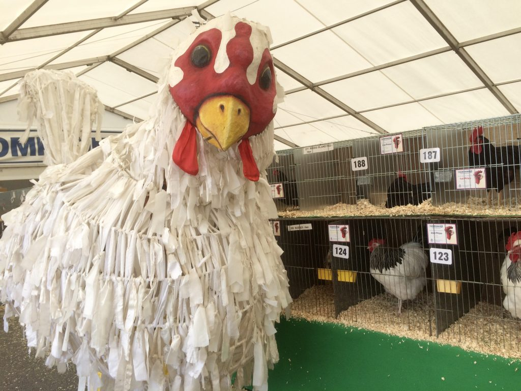 Giant chicken hen in an agricultural show marquee full of prize hens