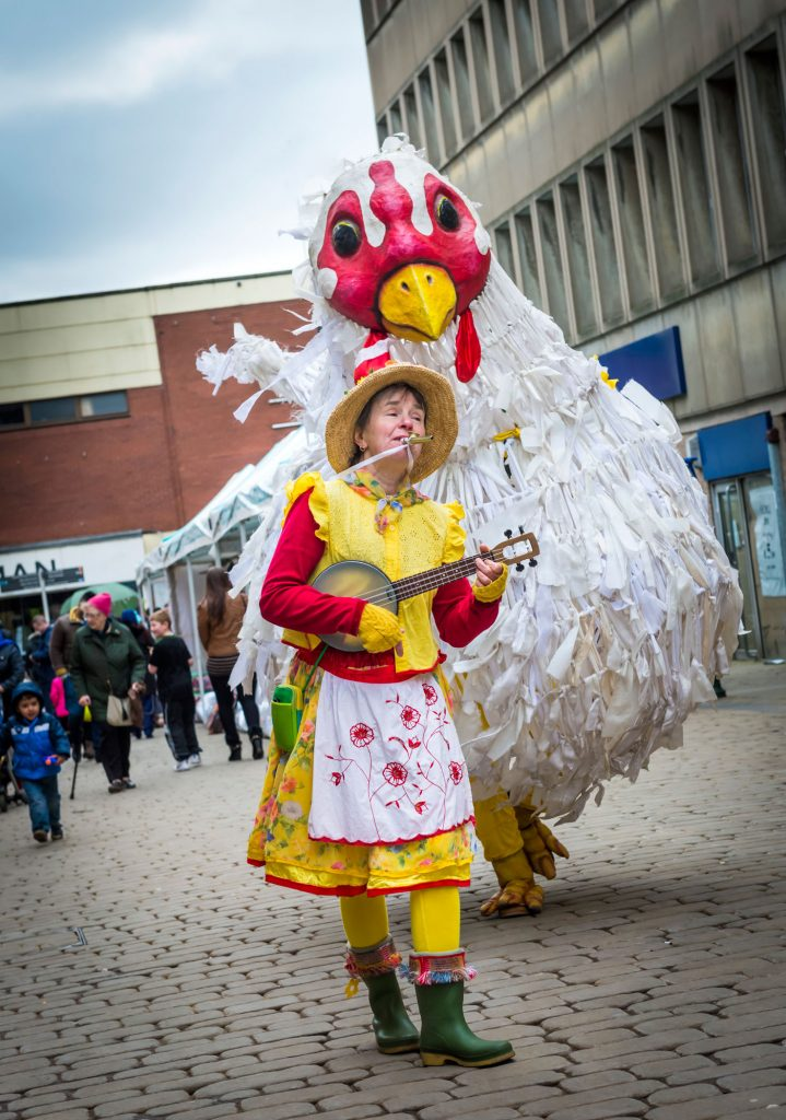 Giant chicken puppet and ukulele musician playing kazoo